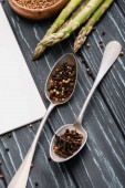 spices in spoons near asparagus on wooden surface