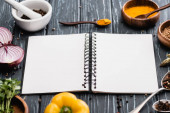 selective focus of fresh colorful vegetables and spices near blank notebook on wooden surface