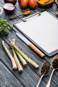 selective focus of blank clipboard near knife and vegetables on wooden surface