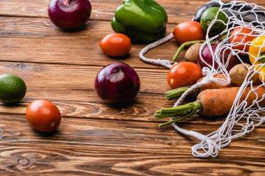 Fresh ripe vegetables scattered from string bag on wooden table stock vector