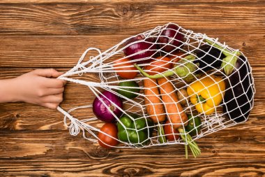 Cropped view of woman holding string bag with fresh ripe vegetables on wooden table stock vector