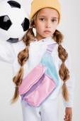 Fotografie Blondes Mädchen in Sportbekleidung posiert mit Fußballball auf weißem Hintergrund