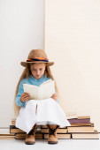fashionable blonde girl in brown hat and boots, white skirt and blue sweater sitting on vintage books and reading near beige wall