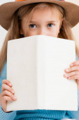 blonde girl in brown hat holding book in front of face