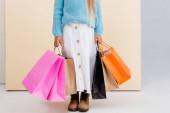 oříznutý pohled na dívku v hnědých botách, bílé sukni a modrém svetru s barevnými nákupními taškami u béžové stěny