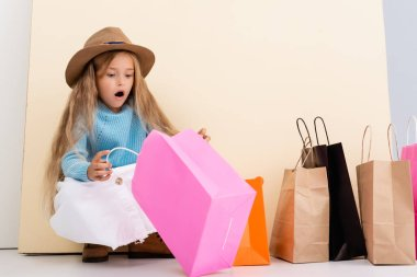 Shocked fashionable blonde girl in brown hat and boots, white skirt and blue sweater looking inside colorful shopping bag near beige wall stock vector