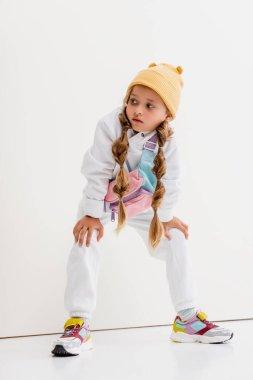 Blonde girl in sportswear posing near white wall stock vector