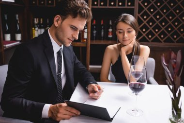 Selective focus of man in suit looking at menu near glasses of wine during dating with girlfriend in restaurant stock vector