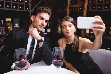 Selective focus of elegant woman taking selfie near boyfriend and glasses of wine in restaurant stock vector
