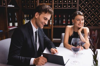 Selective focus of man looking at menu near girlfriend and glasses of wine in restaurant stock vector