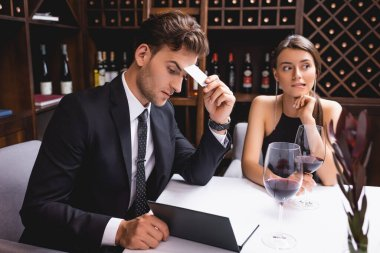 Selective focus of pensive man in suit holding credit card while looking at menu near glasses of wine and girlfriend in restaurant stock vector