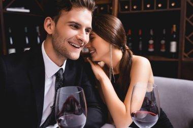 Selective focus of elegant woman embracing boyfriend in suit near glasses of wine in restaurant stock vector