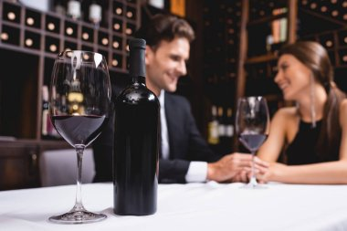 Selective focus of bottle and glass of wine on table near young couple holding hands during dating in restaurant stock vector