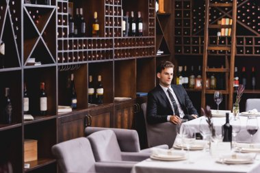 Selective focus of man in formal wear sitting near glass of wine and racks with bottles in restaurant stock vector