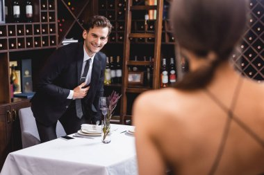 Selective focus of man in formal wear looking at girlfriend during dating in restaurant stock vector