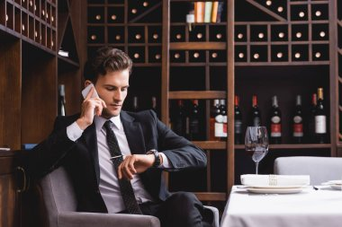 Selective focus of man in suit talking on smartphone and looking at wristwatch near glass of wine in restaurant stock vector
