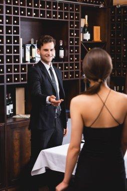 Selective focus of young man in suit meeting girlfriend in restaurant stock vector