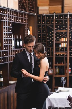 Selective focus of elegant couple dancing in restaurant stock vector