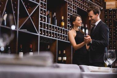 Selective focus of elegant couple dancing near racks with wine bottles in restaurant stock vector