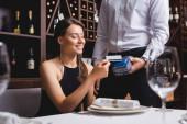 Selektivní zaměření elegantní ženy držící kreditní kartu v blízkosti číšníka s platebním terminálem v restauraci