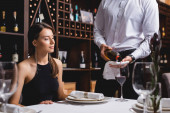 Selective focus of sommelier pouring wine in glass near young woman in restaurant