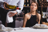 Selective focus of sommelier pouring wine near woman at table in restaurant
