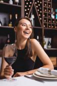 Válogatott fókusz elegáns nő nevetés közben kezében pohár bor étteremben