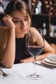 Selektivní zaměření sklenice vína v blízkosti naštvané ženy v restauraci
