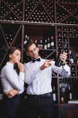 Sommelier pointing with finger ant bottle of wine near pensive colleague in restaurant
