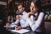 Selektivní zaměření soustředěného psaní someliérů na zápisník u kolegy se sklenicí vína
