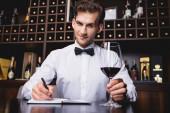 Selektivní zaměření someliéra při pohledu do kamery při držení sklenice vína a psaní do sešitu v restauraci