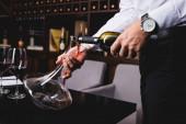 Oříznutý pohled na sommelier v košili nalévání vína z láhve v karafě