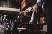 Selective focus of sommelier holding towel and pouring wine in glass on table in restaurant