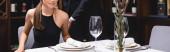 Horizontální obraz muže stojící poblíž přítelkyně a stolu v restauraci