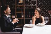 Selektivní zaměření elegantního páru při pohledu na sebe v restauraci