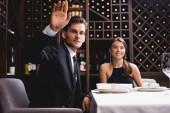 Selective focus of man in suit waving hand near elegant woman in restaurant