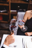 Cropped view of couple toasting with wine during dating in restaurant