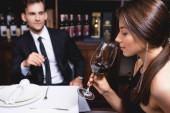 Selektivní zaměření mladé ženy držící sklenici vína v blízkosti přítele v restauraci