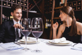 Selective focus of glasses of wine and menu on table near elegant couple in restaurant
