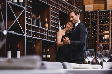 Selective focus of young couple dancing near racks with bottles of wine in restaurant stock vector