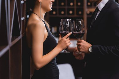 Cropped view of elegant woman holding glass of wine near boyfriend in suit in restaurant stock vector