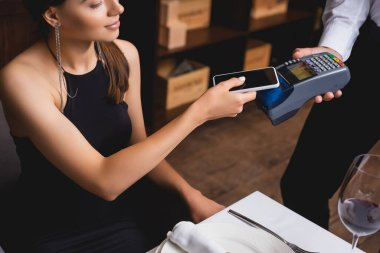 Cropped view of elegant woman paying with smartphone to waiter with payment terminal in restaurant stock vector