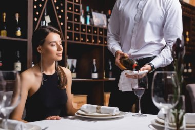 Selective focus of sommelier pouring wine in glass near young woman in restaurant stock vector