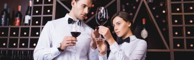 Panoramic shot of sommelier looking at glass of wine near colleague in restaurant stock vector