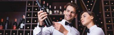 Website header of sommelier holding bottle of wine near colleague in restaurant stock vector