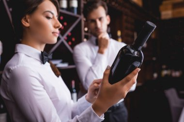 Selective focus of sommelier holding bottle of wine near colleague in restaurant stock vector