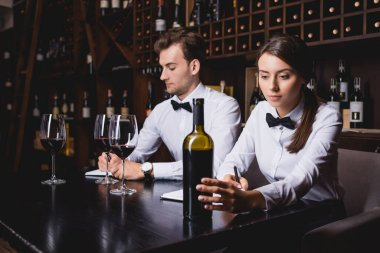 Selective focus of sommeliers noticing on notebooks near bottle and glasses of wine in restaurant stock vector