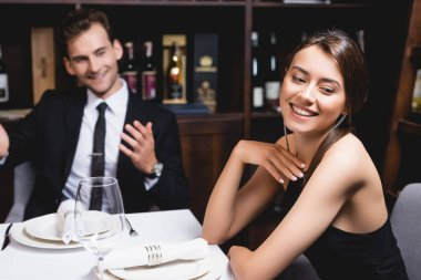 Selective focus of young woman looking away near boyfriend during dating in restaurant stock vector