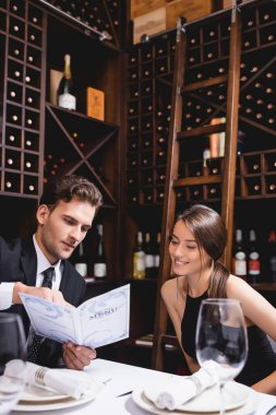 Selective focus of elegant man holding menu near girlfriend in restaurant stock vector