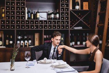 Selective focus of man holding hand of elegant girlfriend in restaurant stock vector